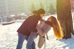 The guy and the girl indulge in the winter, he holds her. A loving couple is playing outside. St. Valentine`s Day stock images