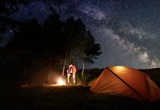 Guy and girl kissing by the fire under bright starry sky which is visible milky way near tent in woods. Guy and girl hikers having a rest by the campfire under a Stock Image