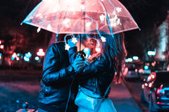 Guy and girl kissing under an umbrella Stock Images