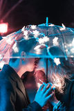 Guy and girl kissing under an umbrella Royalty Free Stock Images