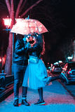 Guy and girl kissing under an umbrella Royalty Free Stock Photography