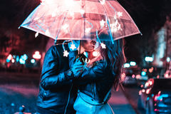Guy and girl kissing under an umbrella Stock Photography