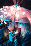 Guy and girl kissing under an umbrella Stock Image
