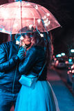 Guy and girl kissing under an umbrella Stock Photo