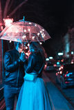 Guy and girl kissing under an umbrella Royalty Free Stock Image