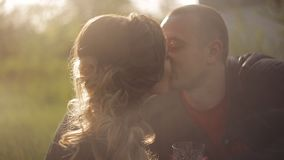 A beautiful couple in love in leather jackets on a picnic. red wine in glasses. Date at sunset in the soft rays of the stock video