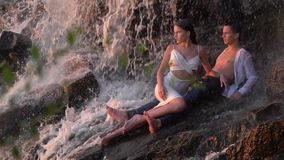A guy with a girl lies under a waterfall and looks at the sunset, slow motion. A guy with a beautiful girl that sits at his feet under a waterfall among the stock video