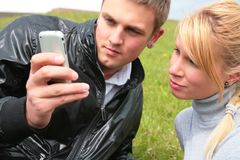 Guy and girl look at device Royalty Free Stock Image