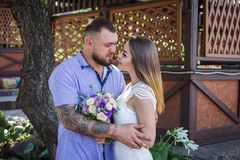 Guy and girl look at each other, portrait of a romantic couple,man and woman kissing in a dramatic light, girl holding flowers in stock image