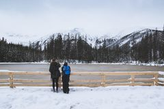 A guy and a girl look at the frozen lake stock photography