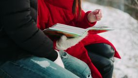 A guy and a girl look at a photo album in winter