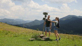 A guy and a girl are looking for a road in the mountains with the help of a pointer.  stock footage
