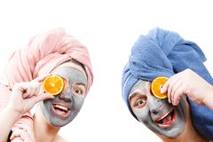A guy with a girl looks at the camera and hold orange slices near the face , mask for skin man and woman, guy with a girl make a royalty free stock photos