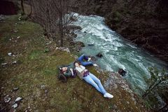 The guy with the girl lying on a cliff by the river. royalty free stock image