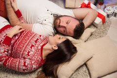 The guy with the girl lying on the floor at the new year Christmas tree royalty free stock photo