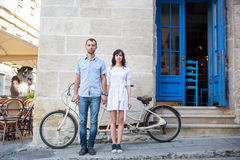 Guy and girl near tandem bike, walls and vintage door Royalty Free Stock Photography