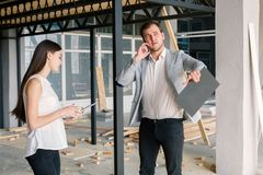 The guy and the girl, near the construction site, the girl uses a tablet, and the guy speaks on mobile phone. stock photo