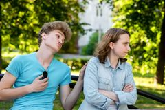 A guy with a girl on a park bench. In summer in the city. The guy asks the girl for forgiveness. The girl is unhappy. A guy with a girl on a park bench. In stock photography