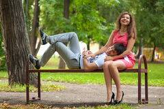 Guy and girl in the park. Funny and lovers guy and the girl on a bench in the park Stock Photography