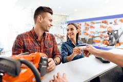 The guy and the girl pay for the purchase of a chainsaw. They are in the shops of tools for gardening. They use a credit card Royalty Free Stock Photography