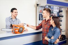 The guy and the girl pay for the purchase of a chainsaw. They are in the shops of tools for gardening. They use a credit card Stock Photography