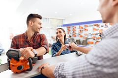 The guy and the girl pay for the purchase of a chainsaw. Stock Photo