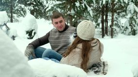 Guy and girl photographed in winter forest. Couple of lovers enjoying in the snow doing a selfie while they are kissing. They are happy, spending a day of stock video