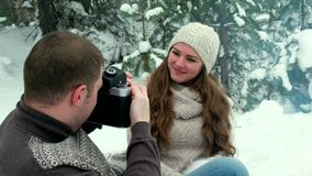 Guy and girl photographed in winter forest. Couple of lovers enjoying in the snow doing a selfie while they are kissing. They are happy, spending a day of stock footage