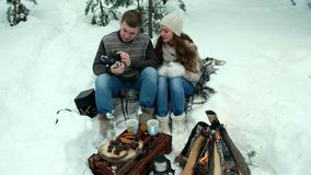 Guy and girl photographed in winter forest. Couple of lovers enjoying in the snow doing a selfie while they are kissing. They are happy, spending a day of stock video footage