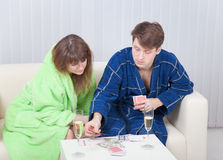 Guy and girl play cards on money at home Royalty Free Stock Image