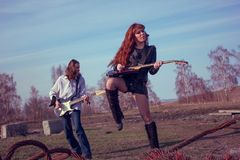 Guy with a girl playing rock on guitars. Guy with girl playing rock on guitars shaking her hair stock photos