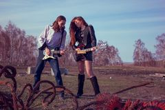 Guy with a girl playing rock on guitars stock photography