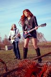 Guy with a girl playing rock on guitars. Guy with girl playing rock on guitars shaking her hair royalty free stock image
