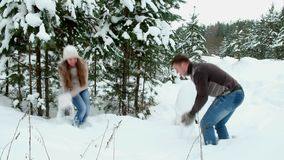 A guy with a girl playing snowballs stock footage