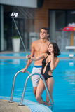 Guy and girl posing against the swimming pool with perfect aqua water and taking selfie photo with monopod on the resort Royalty Free Stock Photos