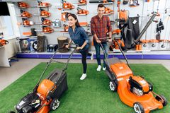 A guy and a girl are posing on the camera with a lawn mower. royalty free stock images