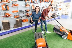 A guy and a girl are posing on the camera with a lawn mower. royalty free stock photography