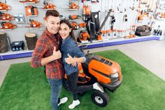 A guy and a girl are posing on the camera with a lawn mower. Royalty Free Stock Photo