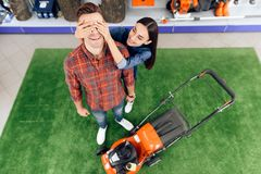 A guy and a girl are posing on the camera with a lawn mower. Stock Photos