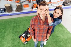 A guy and a girl are posing on the camera with a lawn mower. Stock Photography