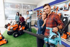 A guy and a girl are posing on the camera with a leaf blower. stock images