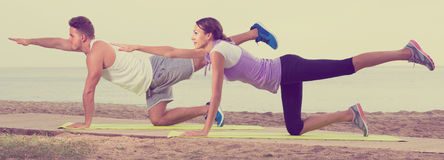 Guy and girl practising yoga poses sitting on beach by sea at da Royalty Free Stock Image