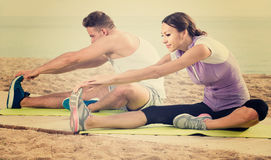 Guy and girl practising yoga poses sitting on beach by sea at da Stock Photos