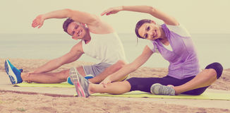 Guy and girl practising yoga poses sitting on beach by sea at da Stock Image