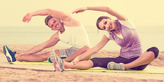 Guy and girl practising yoga poses sitting on beach by sea at da Royalty Free Stock Images