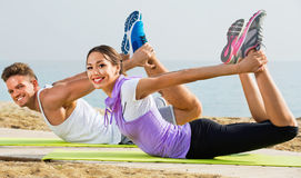 Guy and girl practising yoga poses standing on beach Stock Photo