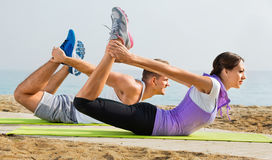 Guy and girl practising yoga poses standing on beach Royalty Free Stock Photography