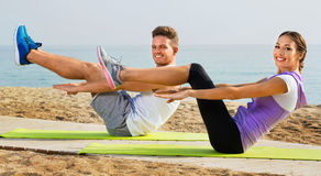 Guy and girl practising yoga poses standing on beach Royalty Free Stock Images