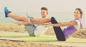Guy and girl practising yoga poses standing on beach. Young guy and girl practising yoga poses standing on beach by sea at daylight Stock Image