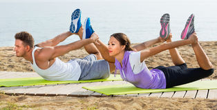 Guy and girl practising yoga poses standing on beach. Young smiling cheerful guy and girl practising yoga poses standing on beach by sea at daylight Stock Photography